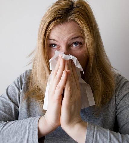 אישה מקנחת את האף האלרגי